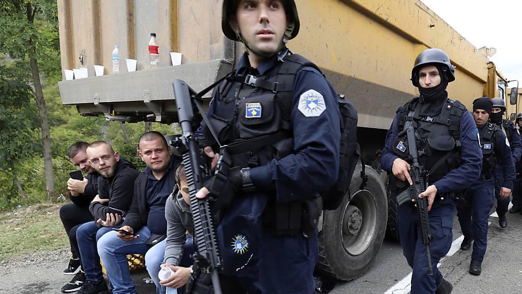 Kosovo-Polizisten patrouillieren an Lastwagen vorbei, wo Kosovo-Serben eine Straße in der Nähe des nördlichen Kosovo-Grenzübergangs Jarinje blockieren. Foto: Bojan Slavkovic/AP/dpa