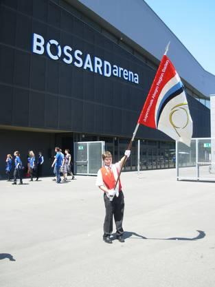 Der Fähnrich zeigt vor der Bossard-Arena die kürzlich erneuerte und angepasste Vereinsfahne