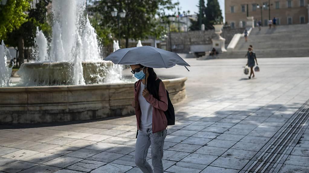 Eine Frau schützt sich bei Temperaturen über 40 Grad auf dem Syntagma-Platz in Athen mit einem Schirm vor Sonne und Hitze. Foto: Angelos Tzortzinis/dpa