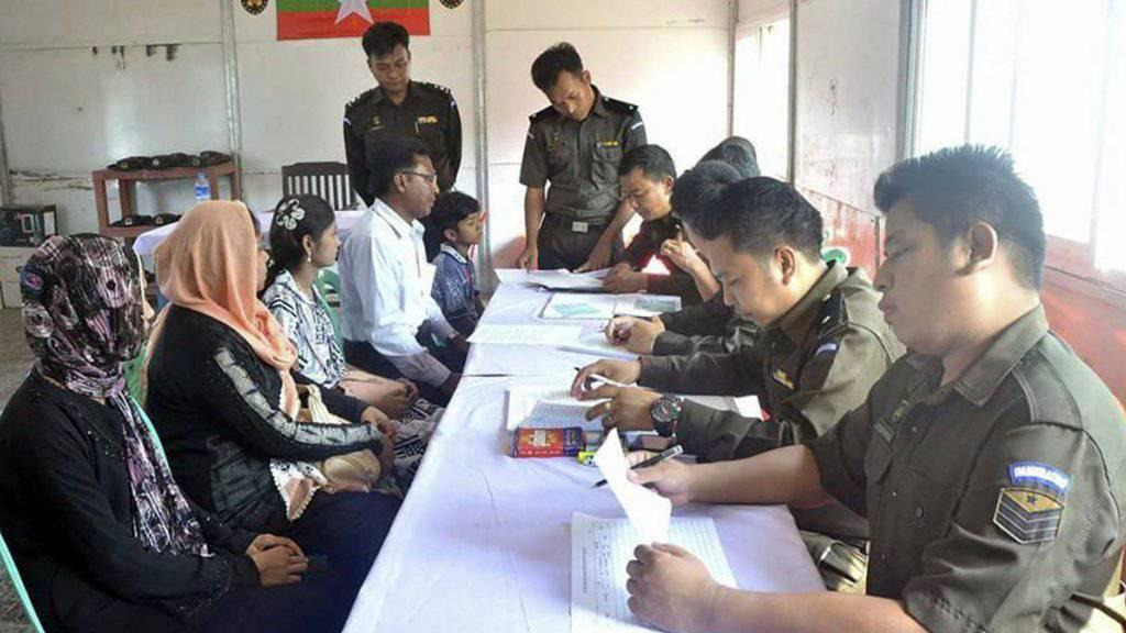 Myanmarische Militärs stellen der Rohingya-Familie Papiere aus.