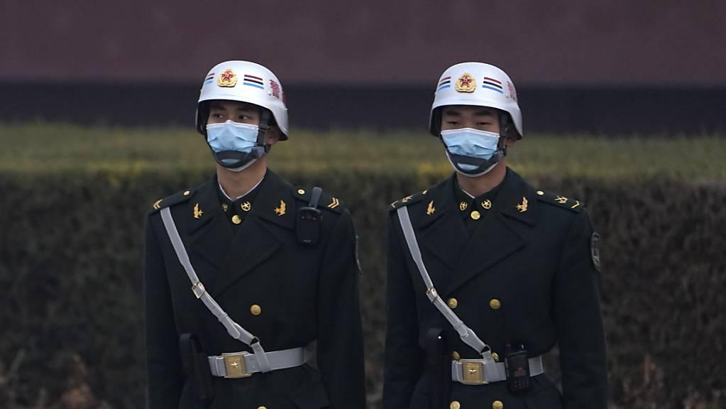 Sicherheitspersonal steht in der Nähe der Großen Halle des Volkes während der Eröffnungssitzung der Jahrestagung des Volkskongresses. Foto: Ng Han Guan/AP/dpa