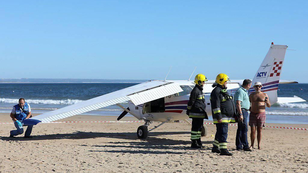 Rettungskräfte prüfen das Kleinflugzeug. Die Maschine hatte bei einer Notlandung an einem belebten Strand in Portugal zwei Badegäste in den Tod gerissen.