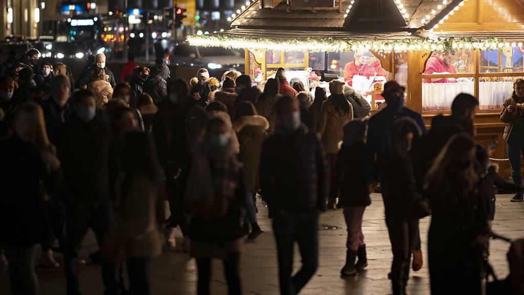 Besucher stehen am Samstag des zweiten Adventswochenendes vor einer Weihnachtsbude am Breitscheidplatz. Im Berliner Bezirk Charlottenburg-Wilmersdorf sind 25 Weihnachtsbuden aufgestellt, als Ersatz für die ausgefallenen Weihnachtsmärkte. Foto: Fabian Sommer/dpa