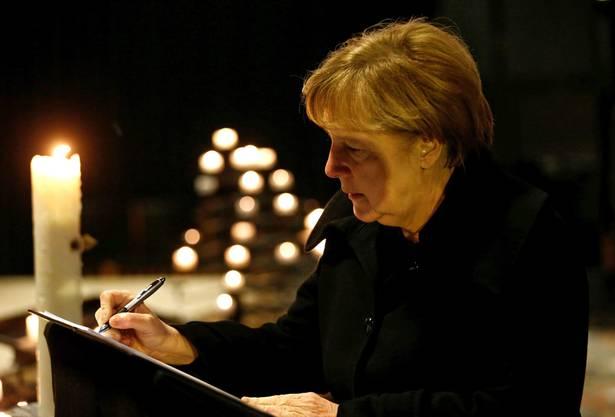 Die Bundeskanzlerin schreibt in der Gedächtniskirche ins Kondolenzbuch.
