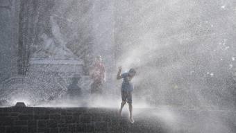 Kinder geniessen das kühle Nass einer Wasserspritze vor dem Winkelried-Denkmal auf dem Dorfplatz in Stans.