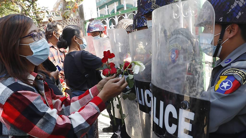 dpatopbilder - Demonstranten überreichen der Polizei Rosen, während vier festgenommene Aktivisten vor Gericht erscheinen. Hunderte von Studenten und Lehrern sind in Myanmar auf die Strasse gegangen, um zu fordern, dass das Militär die Macht an gewählte Politiker zurückgibt. Foto: Uncredited/AP/dpa