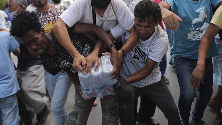 dpatopbilder - Migranten ringen um Wasserflaschen. Foto: Petros Giannakouris/AP/dpa