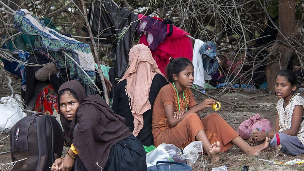 Geflüchtete Rohingya ruhen sich in der Nähe eines Strandes am Boden aus, nachdem ihre Boote an den Andamanen gestrandet war. Nach Monaten auf See sind Dutzende Flüchtlinge der muslimischen Minderheit der Rohingya aus Myanmar in Indonesien gelandet. Foto: Zik Maulana/AP/dpa Foto: Zik Maulana/AP/dpa