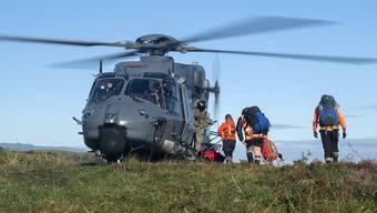 HANDOUT - Rettungshelfer gehen während eines Einsatzen an Board eines Hubschraubers. Zwei in der Wildnis Neuseelands vermisste Wanderer sind nach 18 Tagen lebend gefunden worden. Eine Helikopterbesatzung entdeckte am Mittwoch Rauchschwaden eines Feuers, das die beiden 23-jährigen Dion Reynolds und Jessica O'Connor in ihrem selbsterrichteten Notlager im Busch angezündet hatten. Foto: Cpl Naomi James/New Zealand Defence Force/AP/dpa - ACHTUNG: Nur zur redaktionellen Verwendung im Zusammenhang mit der aktuellen Berichterstattung und nur mit vollständiger Nennung des vorstehenden Credits