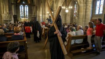 Eine verhüllte Frau trägt an der Karfreitagsprozession in Romont (FR) das Kreuz durch die Kirche.