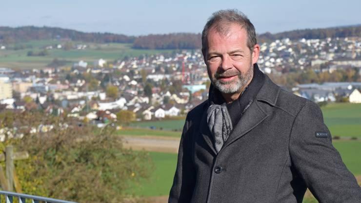 FDP-Parteipräsident und Einwohnerrat Samuel Keller mit Dorf oder Stadt Wohlen im Hintergrund.