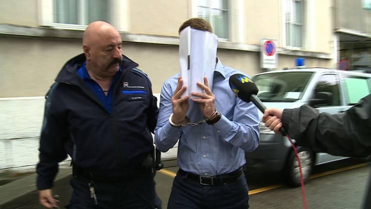 Der Angeklagte wird mit Handschellen ins Gericht geführt.