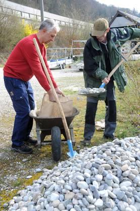 Hansruedi Joss (l.) und Manfred Buchs füllen Steine in Jutesäcke, die danach als Anker an den Bäumchen befestigt werden.