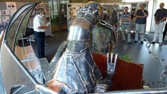 Besucher der Ausstellung Schulprojekte an der Berufsschule hinter dem Brunnen Dragon's Dream. tf