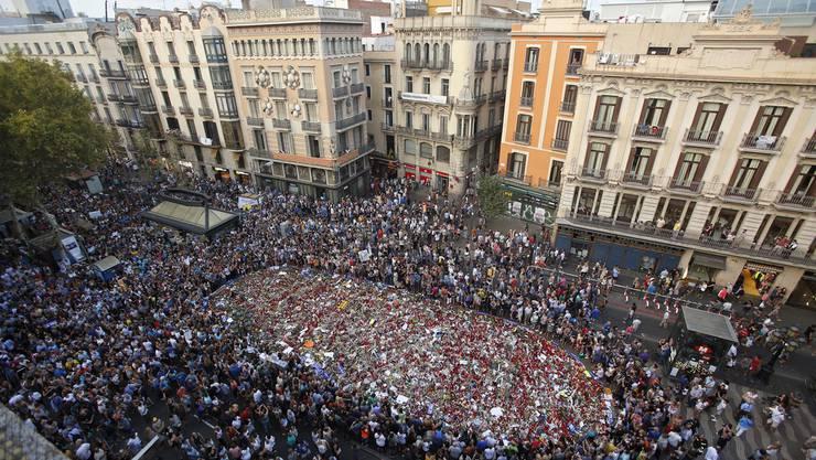 Hier auf der Ramblas geschah die Terrorattacke. Menschen gedenken der Opfer mit Blumen, Kerzen und Plakaten.