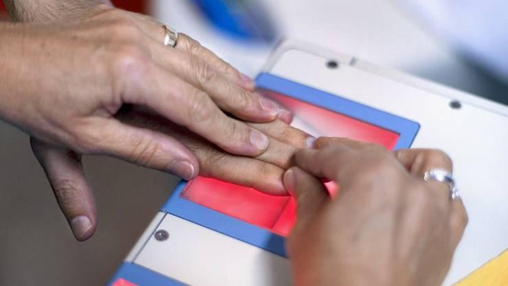 Einem Asylberwerber werden Fingerabdrücke genommen. (Archiv)