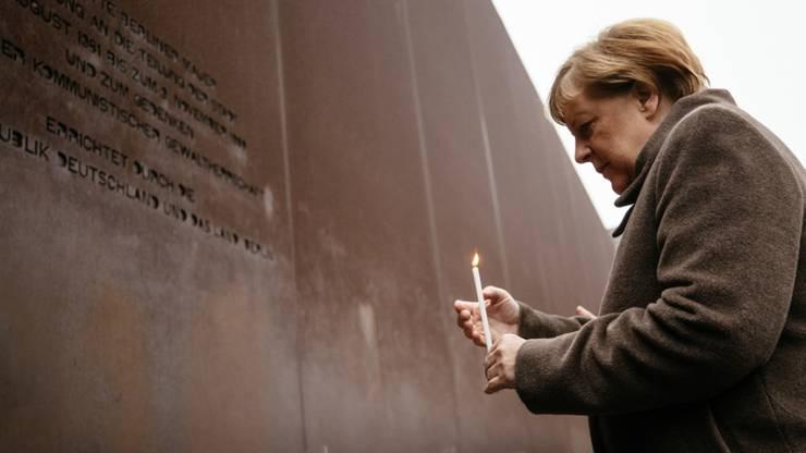 Kanzlerin Angela Merkel mit Kerze am Samstag an der Gedenkfeier zu 30 Jahre Mauerfall in Berlin.