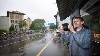 Urs Zimmermann hält die Durchfahrt der Tour de Suisse mit dem Handy fest.