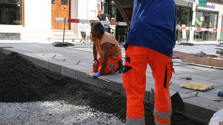 Bauarbeiter verlegen die Natursteinblöcke in der Strassenmitte