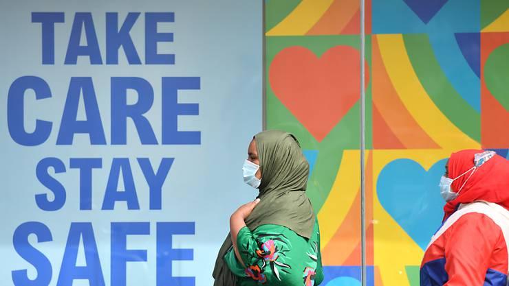 """Frauen mit Kopftuch und Mundschutz gehen in einem Stadtzentrum in Großbritannien an einem Plakat vorbei, das an die Corona-Schutzregeln erinnert: """"Take care, stay safe"""". Foto: Jacob King/PA Wire/dpa"""