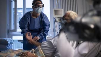 Die Spitäler sind immer noch stark gefordert: Eine Pflegerin misst den Puls eines Covid-Patienten auf der Isolationsstation des Universitätsspitals Zürich.