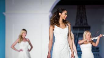 An der Modeschau präsentieren die Models zahlreiche Brautkleider.