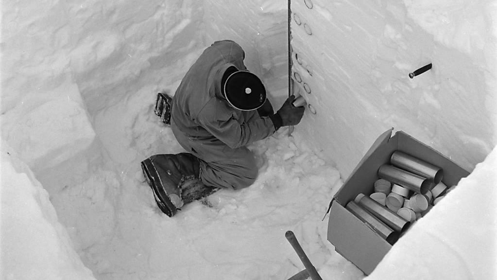 Ein Mitarbeiter des Instituts für Lawinenforschung (SLF) bemisst im Jahr 1953 auf dem Weissfluhjoch in Davos eine Schneedecke. Das SLF warnt seit 75 Jahren in einem Bulletin vor Lawinen. (Archivbild)