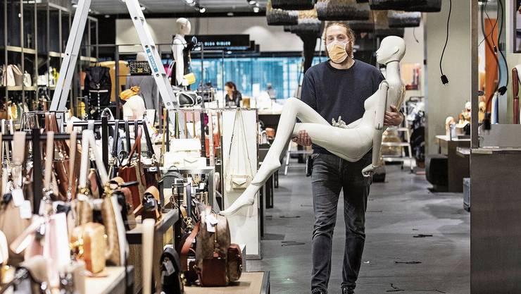 Die Maske ist Teil der Corona-Exit-Strategie: Ein Mitarbeiter des Dekorationsteams läuft mit einer Schaufensterpuppe durch den Globus in Zürich.