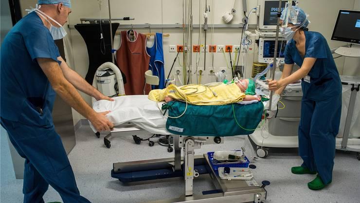 Vor dem Operationssaal wird der kleine Patient von der Anästhesistin Leonie Mnich (l.) vorbereitet. Oberarzt Andreas Zutter hilft ihr, Philipp in den OP zu fahren.
