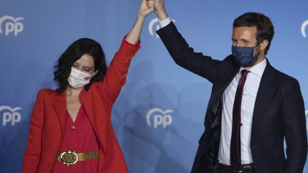 Isabel DÌaz Ayuso (l), Spitzenkandidatin der konservativen Volkspartei (PP), und Pablo Casado (r), Vorsitzender der Partei, feiern den Wahlsieg. Foto: Bernat Armangue/AP/dpa