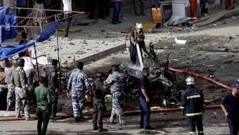 Sicherheitskräfte löschen in Bagdad ein explodiertes Auto