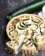 Zutaten für Teig: 130g Mehl20g Parmesan½ TL Salz65g Butter1 EiZutaten für Belag: 1 Zucchini2 Eier150g Schafskäse30g Sonnenblumenkerne15g Parmesan75g SauerrahmÖl Alle Zutaten für den Teig zusammengeben, kneten. Zu einer Kugel formen, mit Frischhaltefolie umwickeln. 30 Minuten im Kühlschrank ruhen lassen. Die Zucchini in dieser Zeit in Scheiben schneiden. Mit Öl anbraten, abkühlen lassen. Den Teig auswallen, in eine Springform legen und Rand formen. Bei 170 Grad 20 Minuten backen. In der Zwischenzeit Eier trennen und das Eiweiss steif schlagen. Schafskäse würfeln und mit Eigelb, Sauerrahm, geriebenem Parmesan und Sonnenblumenkernen verrühren. Salzen und pfeffern. Zum Schluss Zucchini-Scheiben und Eischnee unterheben. Die Masse auf der Springform verteilen, 20 Minuten bei 170 Grad backen.