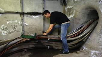 Ein Swisscom-Techniker arbeitet an Kabelsträngen aus Kupfer und Glasfaserleitungen.