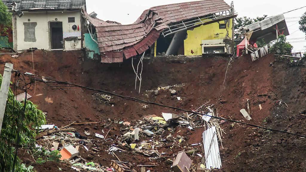 Ruinen eines Hauses hängen über einen Hang in Sumedang, Indonesien, an dem ein Erdrutsch heruntergegangen ist. Foto: Algi Febri Sugita/SOPA Images via ZUMA Wire/dpa