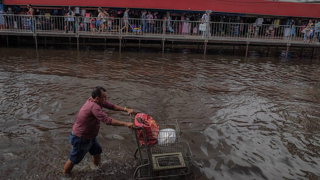 Ein Mann schiebt einen Einkaufswagen durch eine überschwemmte Straße, während Passanten auf provisorisch über dem Wasser angelegten Gehwege spazieren. Foto: Lucas Silva/dpa