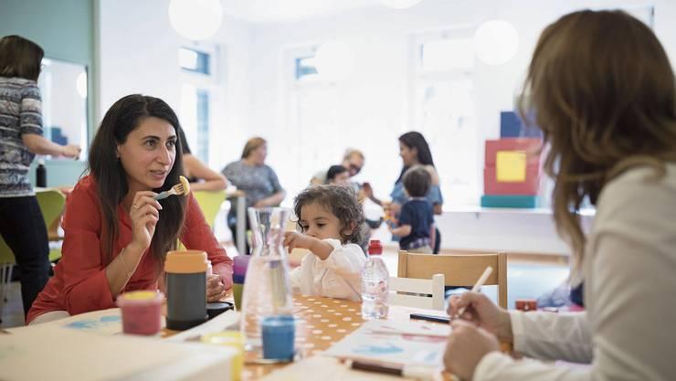 Ausländische Frauen mit ihren Kindern bei einem Integrationskurs der Stadt Zürich.