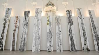 Alois Mosbachers Bäume stehen der Natur folgend aufeinandergesetzt und untereinander austauschbar wie im Wald schräg an der Wand.