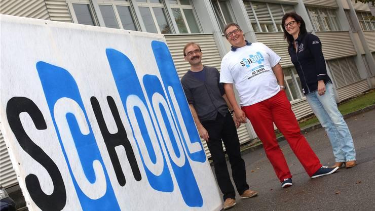 OK 40 Jahre Kreisschule Mittelgösgen: Schulleiter Andreas Basler, OK-Präsident Philipp Müller und die stellvertretende Schulleiterin Brigitte Staub neben dem Logo zur Jubiläumsfeier.