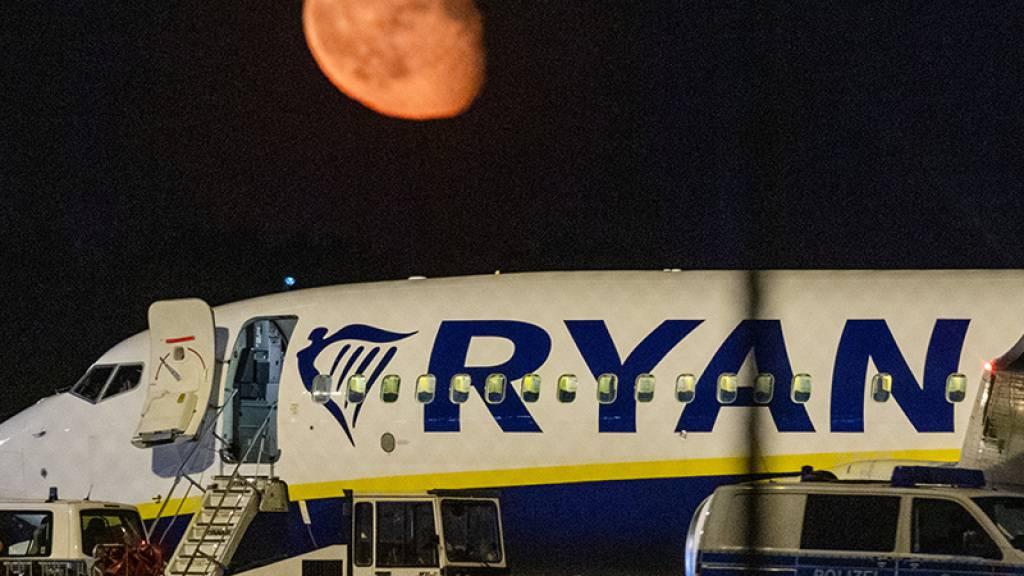 Die Bundespolizei überprüft nach einer außerplanmäßigen Landung einer Ryanair-Maschine am Berliner Hauptstadtflughafen BER das Flugzeug. Im Hintergrund ist der Mond zu sehen. Foto: Christophe Gateau/dpa Foto: Christophe Gateau/dpa