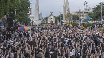 Pro-demokratische Studenten erheben während einer Kundgebung drei Finger als Symbol des Widerstandes. Die Demonstranten haben den Druck auf die Regierung verstärkt, falls diese ihren Forderungen nicht nachkommt. Foto: Sakchai Lalit/AP/dpa