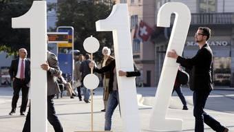 Zwei Zahlen für eine Initiative: Mitglieder der Gewerkschaft Unia auf dem Zürcher Paradeplatz. KEYSTONE