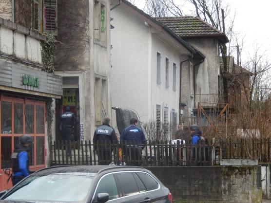 Die Polizisten durchsuchen das Haus.