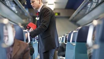 Ein Kondukteur kontrolliert in einem InterCity der SBB die Billette der Fahrgäste (Archiv)