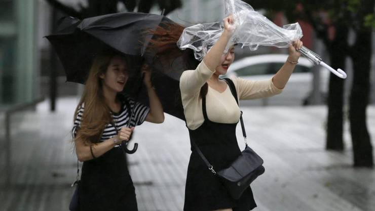 Der starke Wind zerzaust die Regenschirme dieser Japanerinnen.