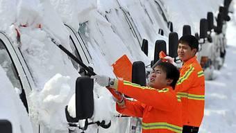 Sicherheitsmänner putzen Schnee von den Autos