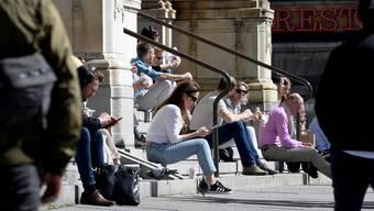 Müssen dieses Jahr wohl zuhause bleiben: Stockholmer geniessen die Frühlingssonne vor dem Royalen Theater. Ins Ausland reisen wird für sie diesen Sommer schwierig. (Bild: Keystone)