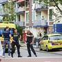 """Polizisten und Krankenwagen stehen am Einsatzort. Beamte haben auf einen 23-jährigen deutschen Mann geschossen, der verwirrtes Verhalten zeigte und drohte, sich und die Polizei zu verletzen. Der Mann erlag später seinen Verletzungen. Foto: """"ginopress B.V.""""/ANP/dpa"""
