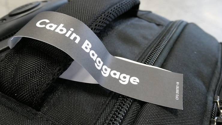 """ARCHIV - Ein Anhänger mit der Aufschrift """"Cabin Baggage"""" (Kabinengepäck) am Haltegriff eines kleinen Koffers. Foto: Andrea Warnecke/dpa-tmn/dpa"""