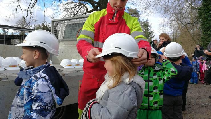 """Zuerst setzt Maurerlehrling Pascal Bätscher den Kindern Helme auf. Diese können die Kinder nachher behalten. """"Zum Spielen"""", sagt Bätscher."""