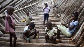 Willkommene Gaumenfreude: Haitianische Kinder essen Mangos in einem Schiffsrumpf (Archiv)